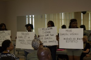 young ladies held up signs with statistics on Domestic Violence